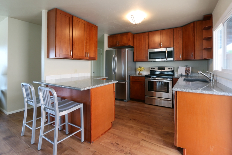 70 East Lipoa Street open kitchen with new stainless steel appliances and new maple hardwood